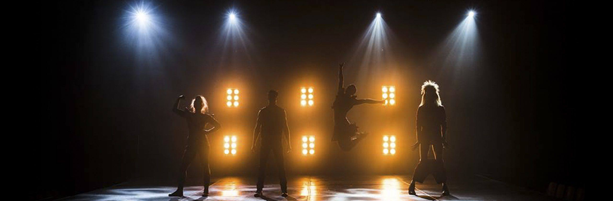 circus artists backlit with a dramatic lighting design